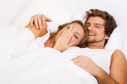 Couple smiling in bed together