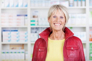 Female Pharmacist Wearing Jacket While Smiling In Pharmacy